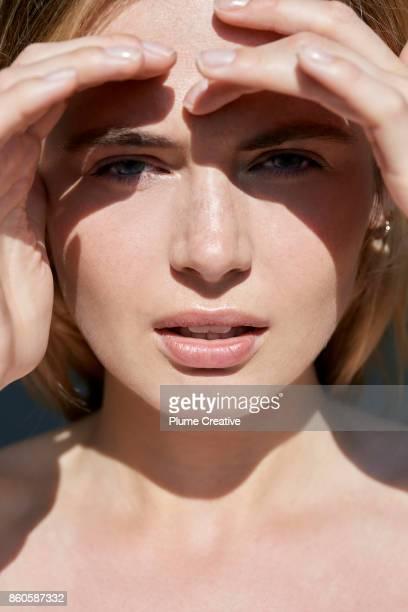 woman shielding eyes from sun - queimadura pele imagens e fotografias de stock
