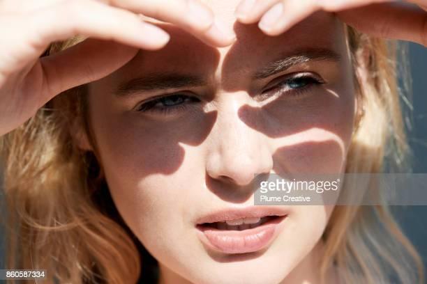 woman shielding eyes from sun - mujeres hot fotografías e imágenes de stock