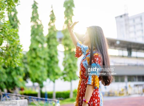 woman shielding eyes while standing against trees - anuwat somhan stock photos and pictures