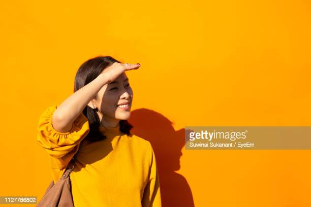 woman shielding eyes while standing against yellow wall - shielding stock pictures, royalty-free photos & images