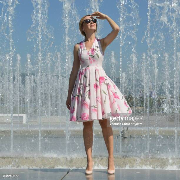 Woman Shielding Eyes While Standing At Fountain