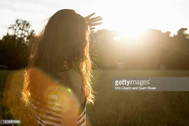 woman shielding her eyes from sun - esperar fotografías e imágenes de stock