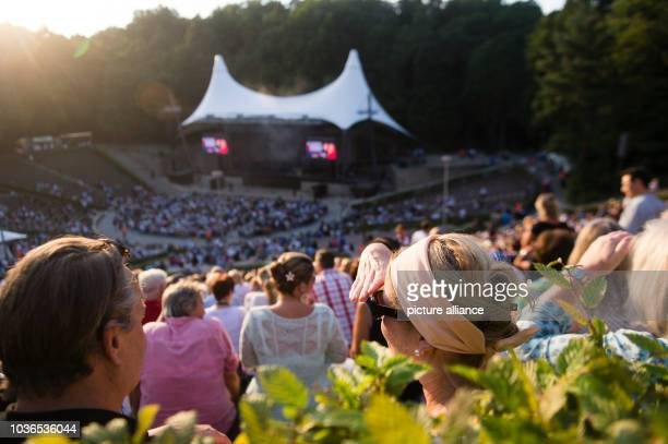 A woman shields her eyes from the evening sun during a concert by Albano und Romina Power at the Waldbuehne in Berlin Germany 21 August 2015 Photo...