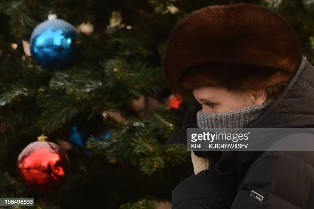 A woman shields her face against the freezing outdoors as she walks past a New Year tree in central Moscow on December 18 2012 The temperatures in...