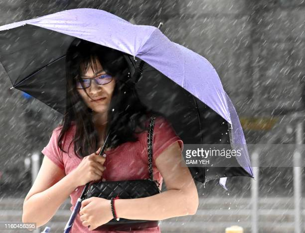 A woman shields herself with an umbrella as she walks in New Taipei City in rain brought by Typhoon Lekima as it passes northeastern Taiwan on August...