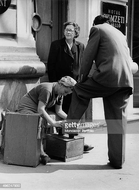Woman shining the shoes of a man in a street of Budapest Budapest 1958