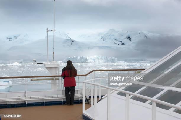 Woman ship view Antarctic Peninsula ice filled Neko Harbor mountain glacier Antarctica