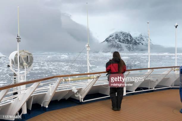 woman ship view antarctic peninsula ice filled neko harbor mountain glacier antarctica - milehightraveler stock pictures, royalty-free photos & images