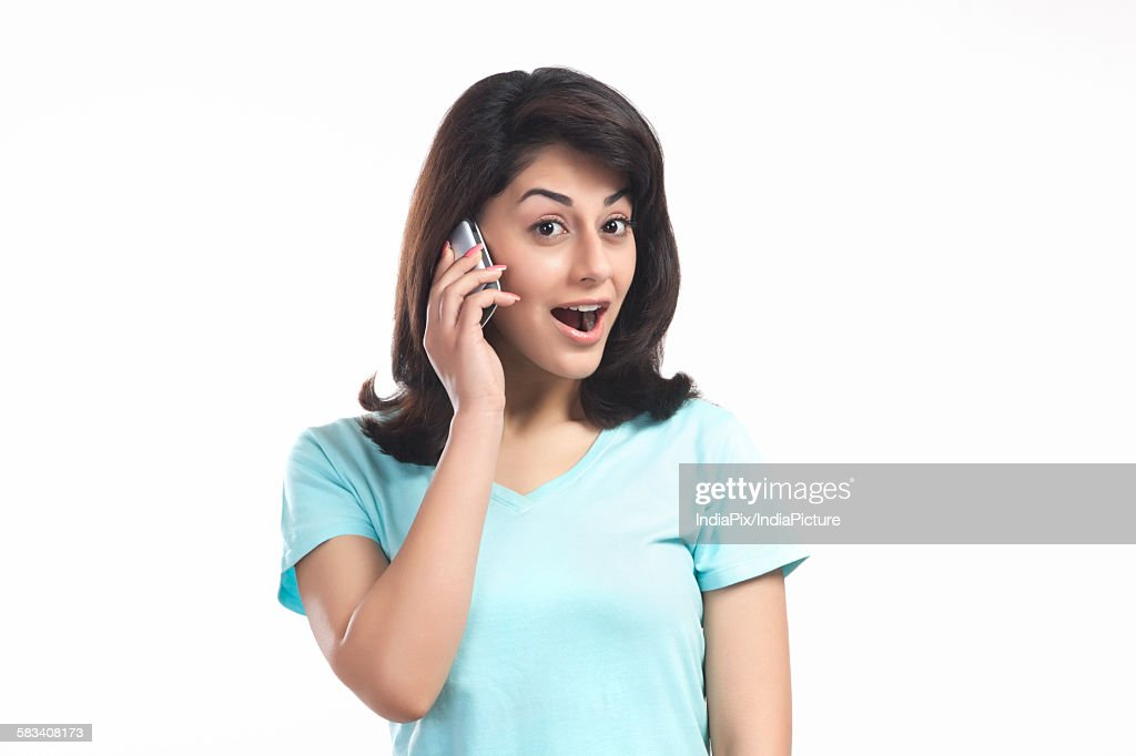 Woman shocked while talking on a mobile phone : Stock Photo