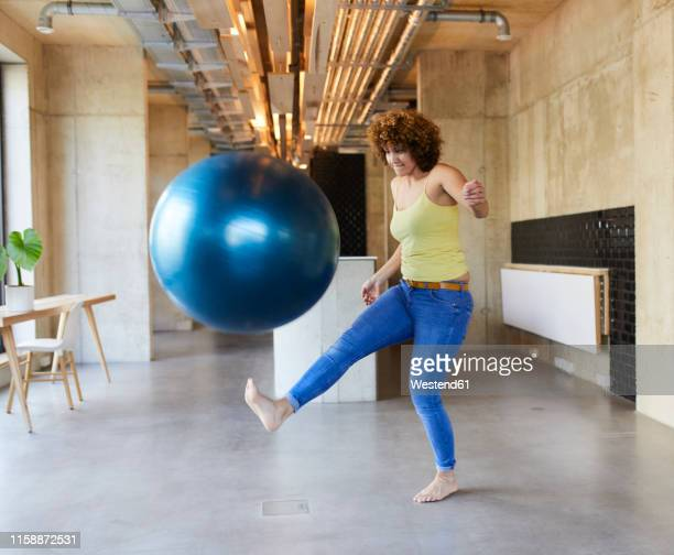 woman shooting a fitness ball in modern office - kicking stock pictures, royalty-free photos & images