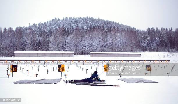 woman shooting at biathlon competition against clear sky - paulien tabak stock pictures, royalty-free photos & images
