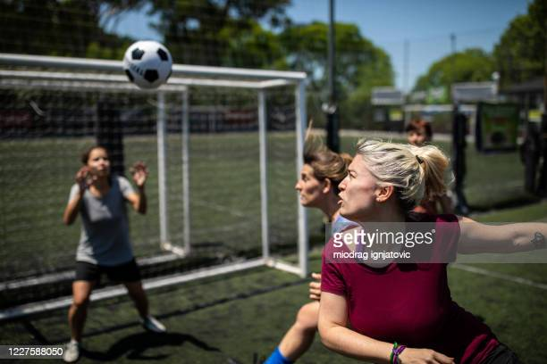 woman shooting at goal after free kick on soccer field - corner kick stock pictures, royalty-free photos & images