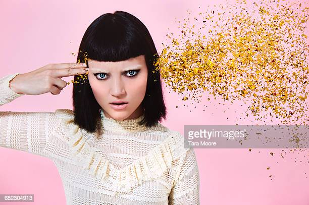 woman shooting glitter through head