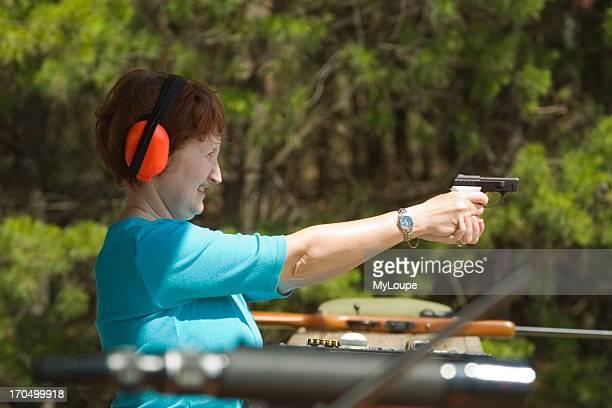 Woman Shooting Hand Gun At Target At Shooting Range In Ocala National Forest Ocala Florida USA