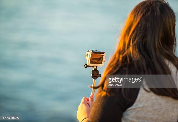 Tiro de mulher com GoPro Câmera na praia