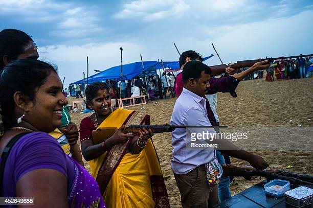 A woman shoots balloons unseen using an air gun on Marina Beach in Chennai Tamil Nadu India on Sunday July 20 2014 Optimism about a revival in Asias...