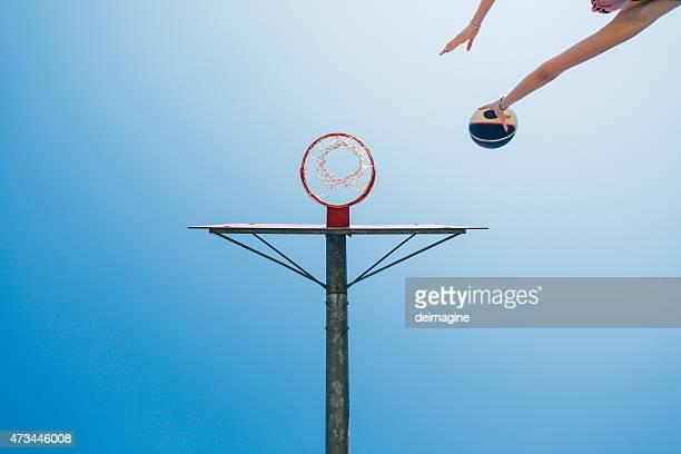 Frau schießt auf Ziel in dem Basketballplatz