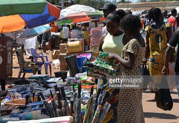 Woman shop at a stall in a market in the central African capital Bangui on October 2 as Muslim traders who fled at the start of the year to...