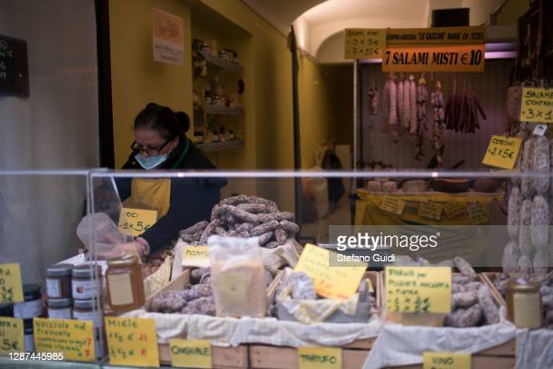 A woman shopkeeper wearing a protective mask fixes the cheese and salami shop in Via Garibaldi on November 24 2020 in Turin Italy While the whole...