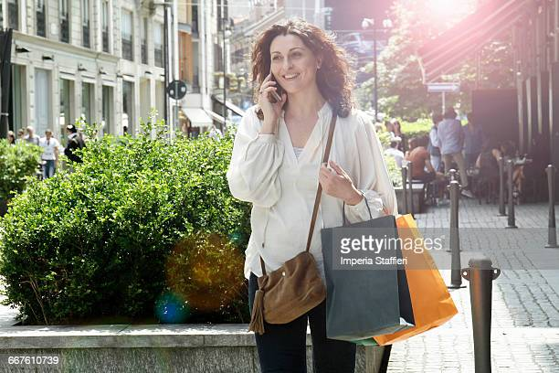Woman shopper strolling on street talking on smartphone, Milan, Italy