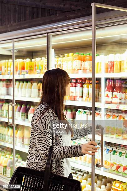Woman shopping at freezer section in supermarket
