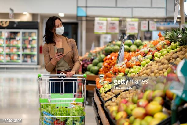 woman shopping at the grocery store wearing a facemask - groceries stock pictures, royalty-free photos & images