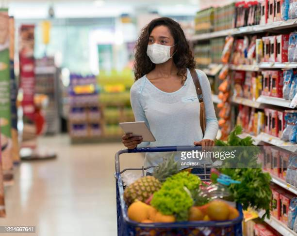woman shopping at the supermarket wearing a facemask - supermarket stock pictures, royalty-free photos & images
