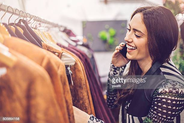 Woman shopping clothes and talking on the phone