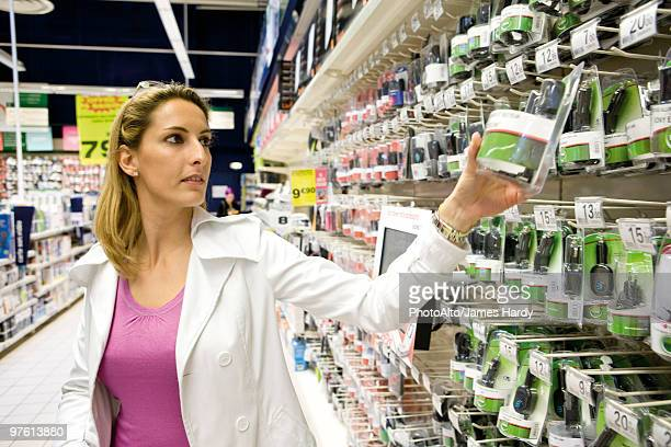 woman shopping for cell phone charger - electronics store stockfoto's en -beelden