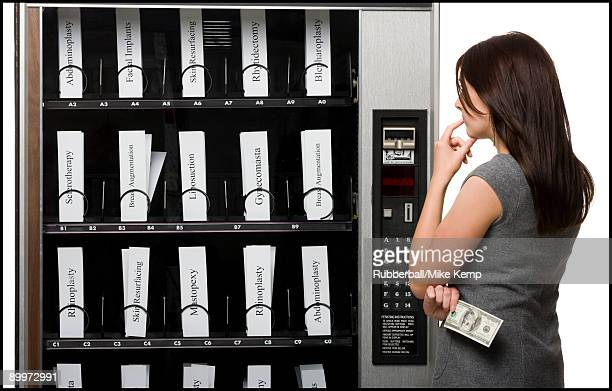 woman shopping for cosmetic surgery procedures from a vending machine - liposuction stock photos and pictures