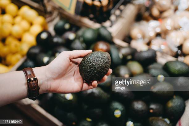 woman shopping for fresh fruit and vegetables in supermarket, close up of her hand choosing avocados - produce aisle stock pictures, royalty-free photos & images