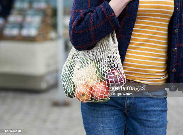 woman shopping for fresh fruit and vegetables with reusable plastic free bag, close up. - environmentalism stock pictures, royalty-free photos & images