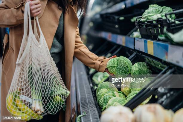 woman shopping for fresh organic fruits and vegetables in supermarket - sustainable lifestyle stock pictures, royalty-free photos & images