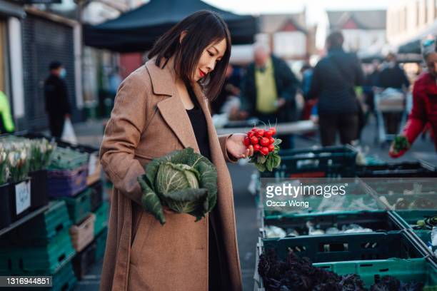 woman shopping for fresh organic vegetables at farmer market - crucifers stock pictures, royalty-free photos & images