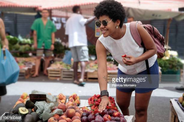 woman shopping for fruits at a street market in the city of rio de janeiro - street market stock pictures, royalty-free photos & images