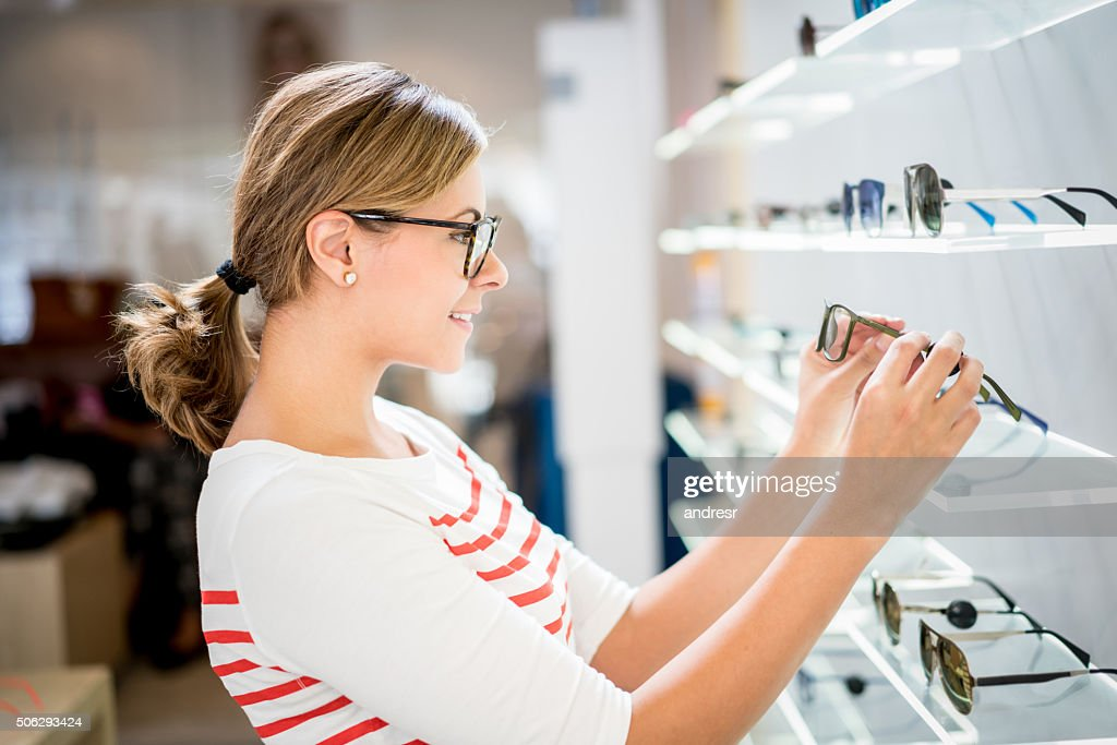 Woman shopping for glasses at the optics : Stock Photo