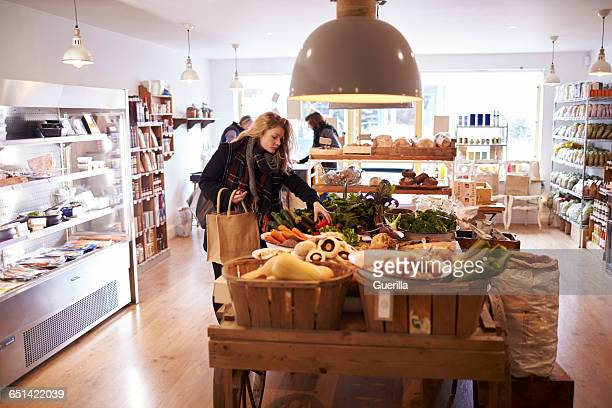 woman shopping for organic produce in delicatessen - wide shot stock pictures, royalty-free photos & images