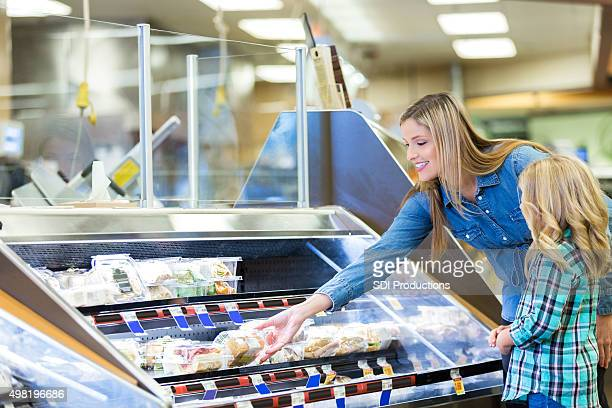 woman shopping for prepared foods in deli with daughter - delicatessen stock pictures, royalty-free photos & images