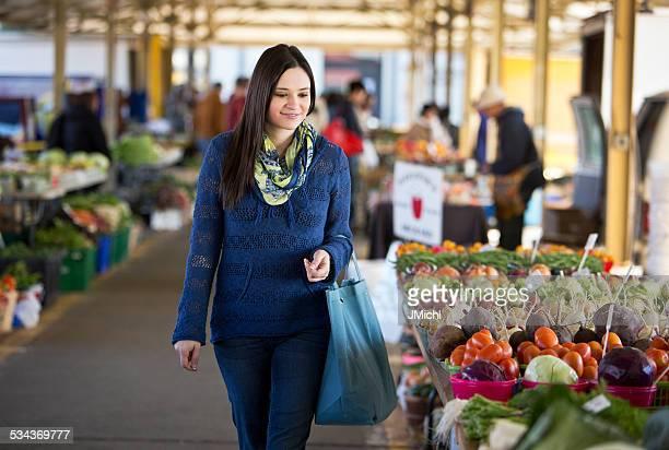 Mulher às compras para produzir em um mercado de agricultores.