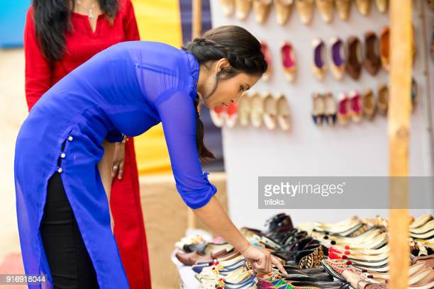 woman shopping for sandal at street market - faridabad stock pictures, royalty-free photos & images