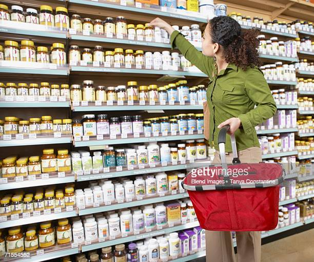 woman shopping for vitamins - nutritional supplement stock pictures, royalty-free photos & images