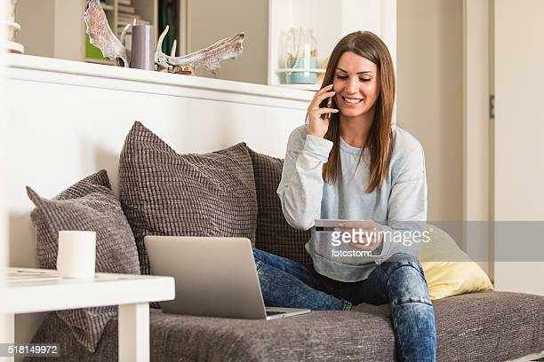 Woman shopping from home, talking on the mobile phone