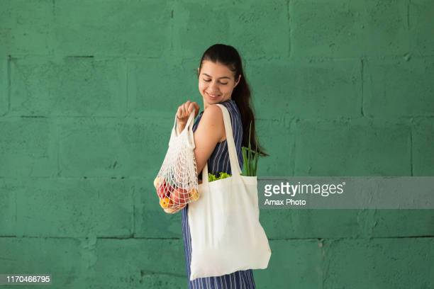 woman shopping fruits and vegetables with reusable cotton eco produce bag. zero waste lifestyle concept - ecosystem stock pictures, royalty-free photos & images