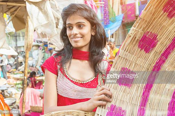 Woman shopping handmade baskets at street market in India