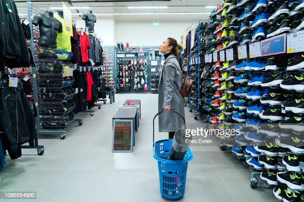 Woman shopping in a sport store, checking out of prices