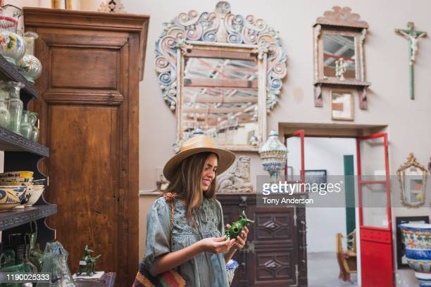 woman shopping in antique store - brown purse stock pictures, royalty-free photos & images