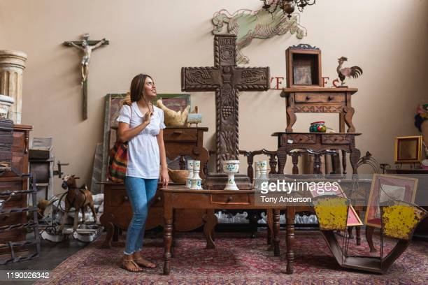 woman shopping in antique store - cristianismo imagens e fotografias de stock
