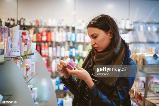 woman shopping in cosmetics shop - toiletries stock pictures, royalty-free photos & images