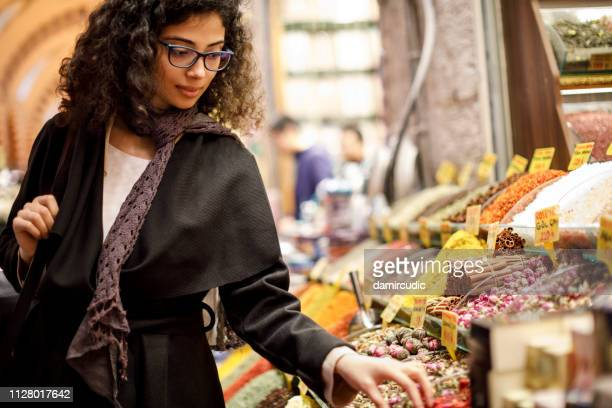woman shopping in spice shop in grand bazaar, istanbul, turkey - street market stock pictures, royalty-free photos & images