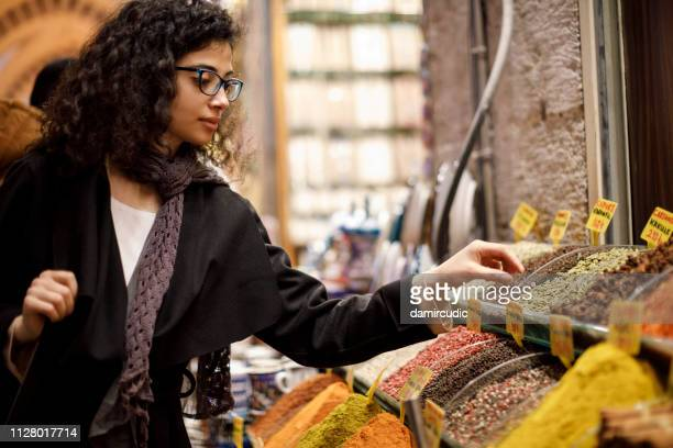 woman shopping in spice shop in grand bazaar, istanbul, turkey - nut food stock pictures, royalty-free photos & images